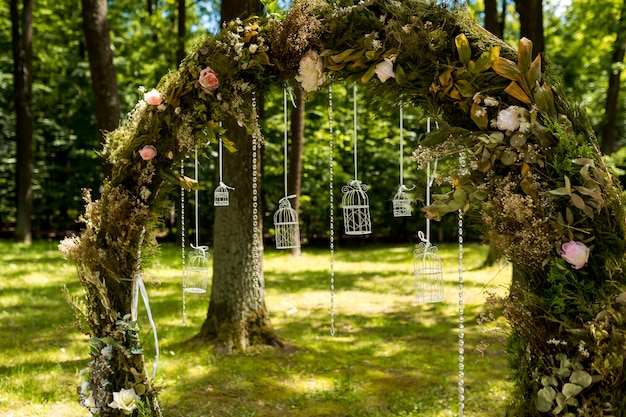 Arch for the wedding ceremony. decorated with flowers and greenery. is located in a pine forest. just married. Premium Photo