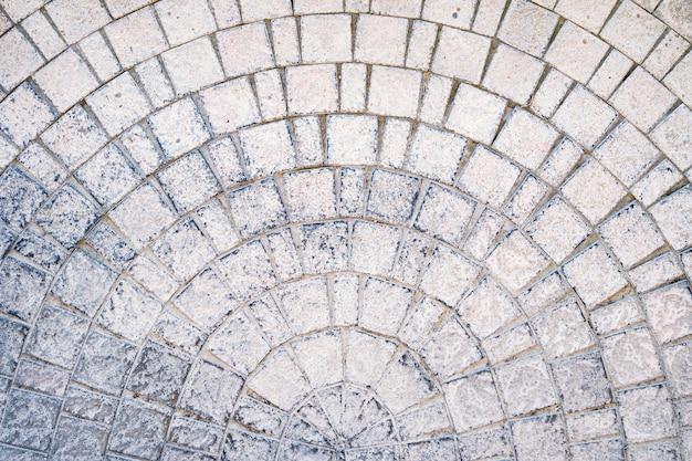 歩道のテクスチャにエッジコースがあるアーチ型の石畳の舗装道路 無料写真