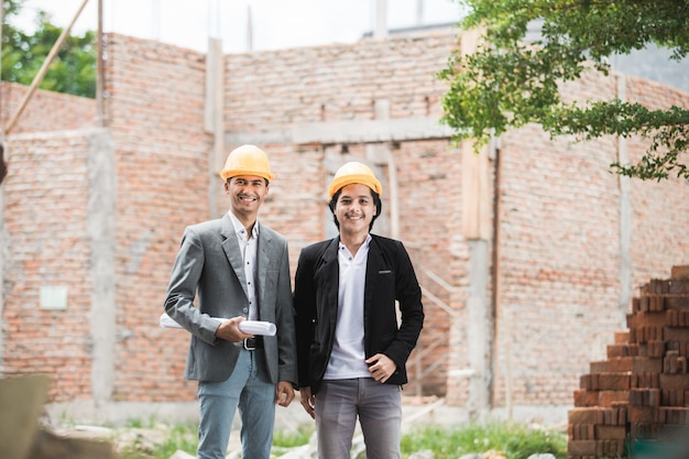 Architect and builder standing in front of unfinished house Premium Photo