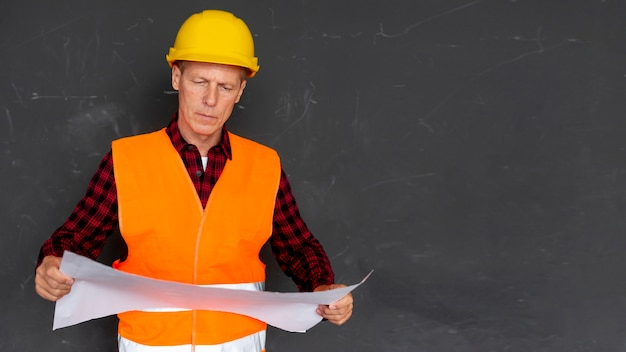 Architect checking plans with copy space Free Photo