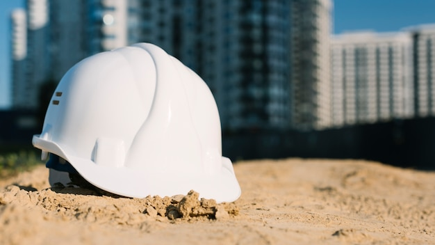Architect concept with safety helmet on sand Free Photo