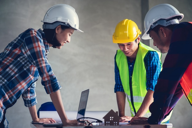 Architect & engineer working drawing document about project planning and progress of work schedule on the home building construction site Premium Photo