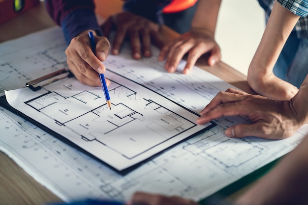 Architect & engineer working drawing document about project planning and progress of work schedule on the home building construction site , Premium Photo