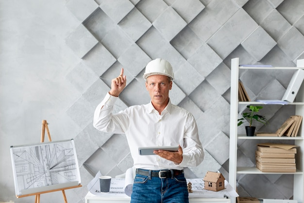 Architect in his office pointing up Free Photo