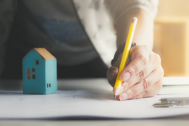 Architect man holding pencil working with laptop and blueprints for architectural plan, engineer sketching a construction project and property concept. Premium Photo