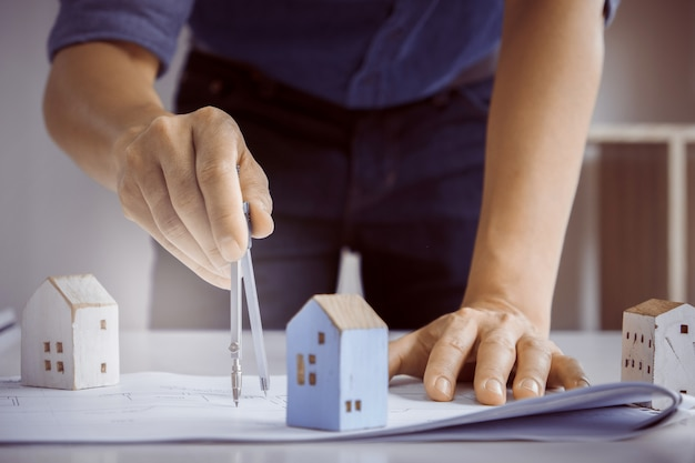 Architect man working with compasses and blueprints for architectural plan,engineer sketching a construction project concept. Premium Photo