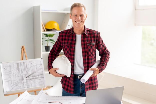 Architetto che sorride mentre posando all'ufficio Foto Gratuite