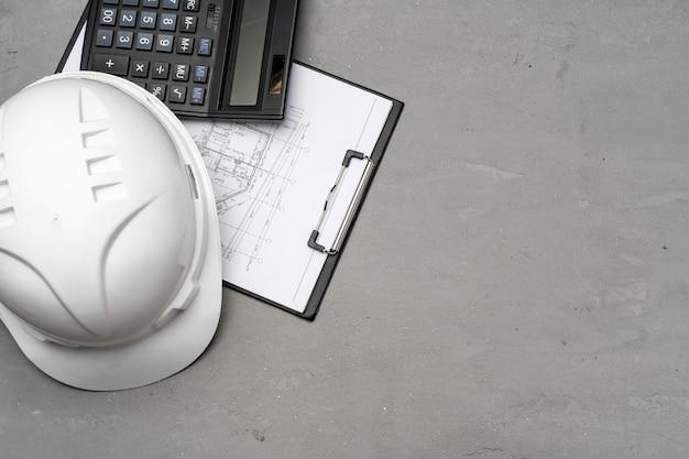 건축가 도구는 안전모, 청사진 및 계산기 평면도로 부각됩니다. 프리미엄 사진
