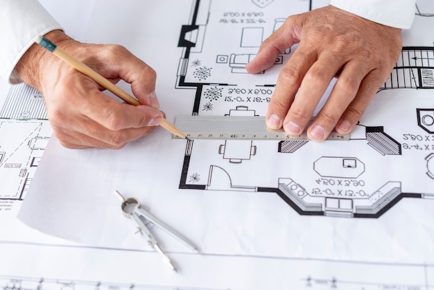 Architect using ruler on his project close-up Free Photo