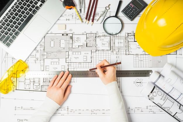 architect using ruler on blueprint photo free download