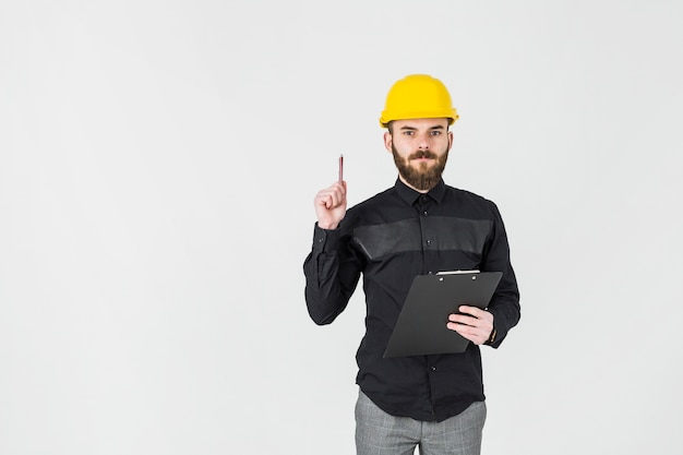 An architect wearing hardhat holding clipboard over white background Free Photo