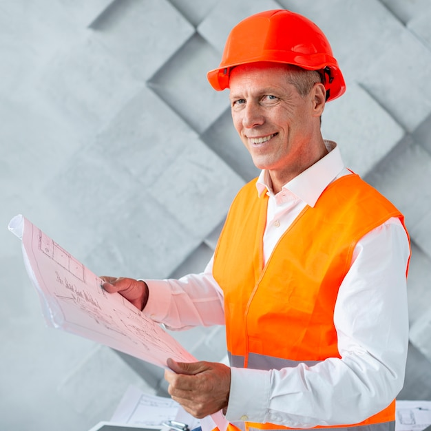 Architect with safety helmet looking at the camera Free Photo