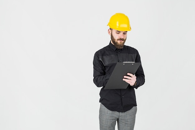 Architect writing on clipboard standing against white background Free Photo