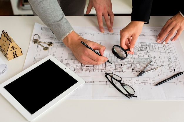 Architects analysing plan with magnifier Free Photo