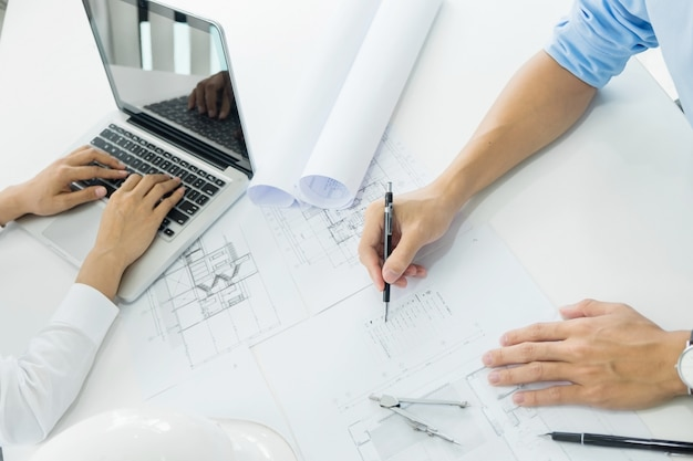 Architects engineer discussing at the table with blueprint closeup architects engineer discussing at the table with blueprint closeup on hands and project print malvernweather Choice Image