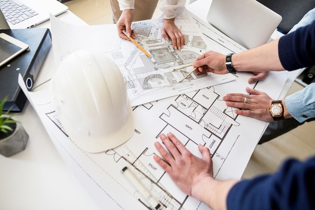 Инженер-архитектор обсуждает за столом с планом Premium Фотографии