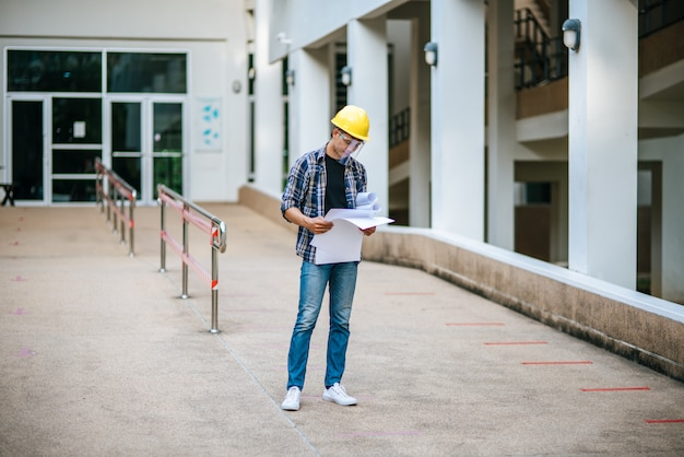 Architects hold the building plan and check the work. Free Photo