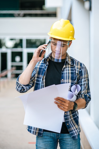 Architects hold floor plans and talk on the phone. Free Photo