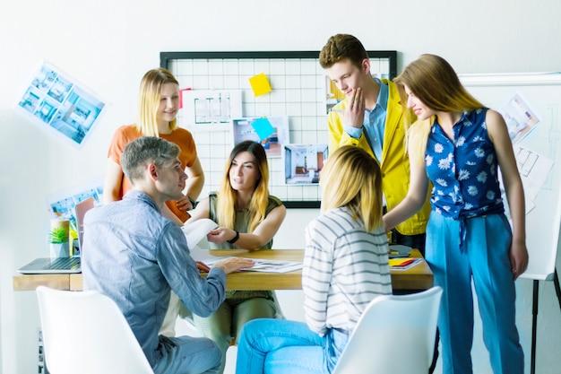 建築家のインテリアデザイナーの創造的な人々マネージャーオフィスワーカーのコンセプトアイデア新しいアパートの設計プロジェクトについて議論します。カラフルな白い部屋でチーム作業ビジネス会議会議プレゼンテーション。 Premium写真