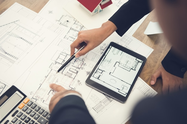 Architects or interior designers discussing floor plan blueprints Premium Photo