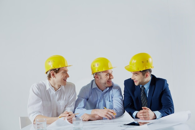 Architects with yellow helmets laughing Free Photo