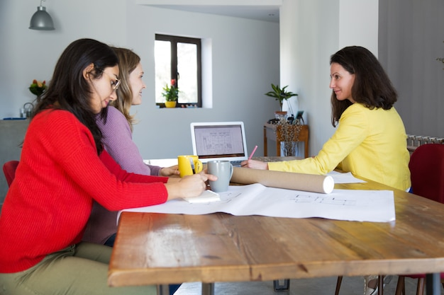 Architects working with drawings at desk in office Free Photo