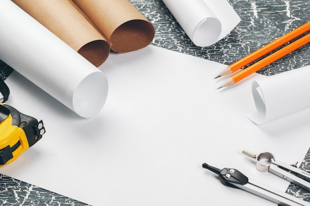 Architectural blueprints and blueprint rolls and a drawing instruments on the worktable. Premium Photo