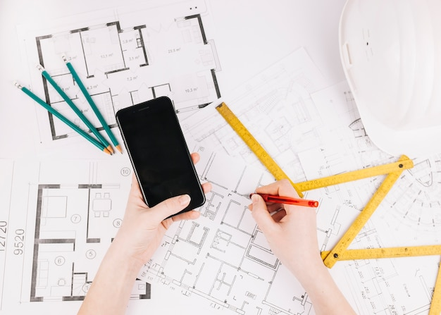 Architecture concept with building plan and smartphone Free Photo