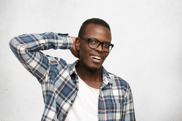 Ты шутишь, что ли? счастливый ошеломленный молодой афроамериканский хипстер в очках и клетчатой рубашке смотрит в волнении, удивленный хорошими неожиданными новостями, держа руку за головой Бесплатные Фотографии