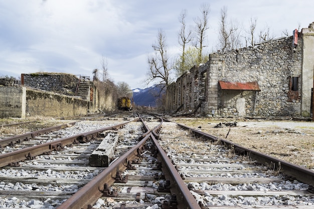 Area with train tracks surrounded by old concrete buildings under a cloudy sky Free Photo