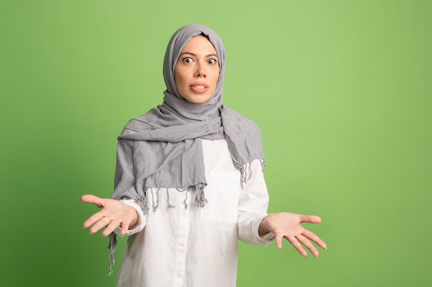 Argue, arguing concept.arab woman in hijab. portrait of girl, posing at green studio background. young emotional woman. the human emotions, facial expression concept. front view. Free Photo