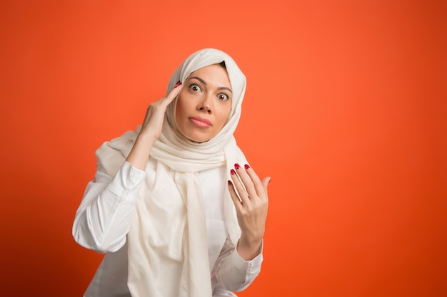 Argue, arguing concept.arab woman in hijab. portrait of girl, posing at. red studio background. young emotional woman. the human emotions, facial expression concept. front view. Free Photo
