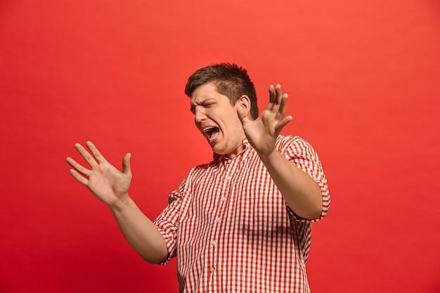 議論、議論の概念。赤いスタジオの背景に分離された面白い男性の半分の長さの肖像画。カメラを見て若い感情的な驚きの男。人間の感情、表情の概念。正面図 無料写真