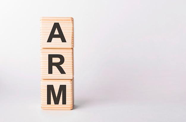 Буквы arm из деревянных блоков в форме столба на белом фоне, копией пространства Premium Фотографии