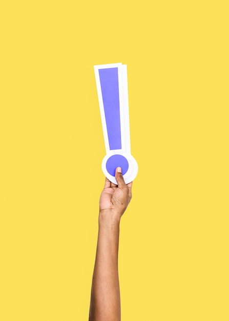 Arm raised and holding exclamation mark icon Free Photo