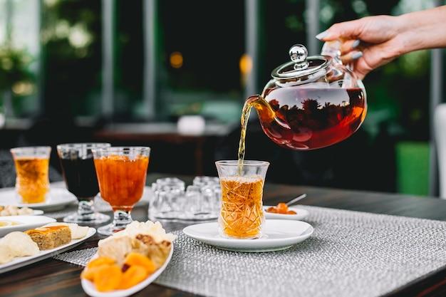 Вид спереди девушка наливает чай из чайника в бокал armoud с вареньем и сладостями на столе Бесплатные Фотографии