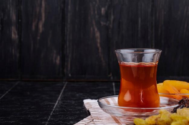 Вид сбоку armudu стакан чая с сухофруктами на черном фоне деревенском Бесплатные Фотографии