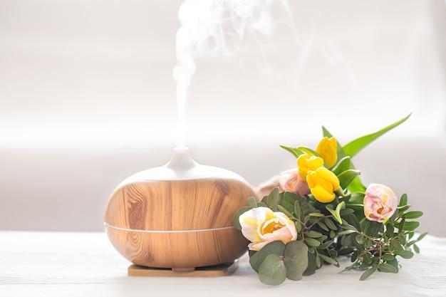 Лампа-диффузор ароматического масла на столе на размытом фоне с красивым весенним букетом тюльпанов. Бесплатные Фотографии