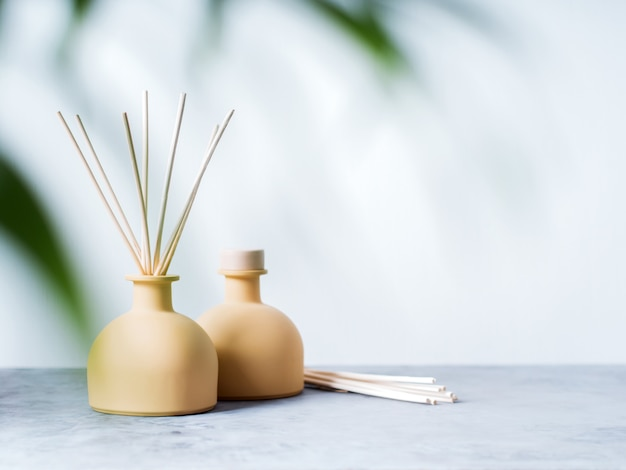 Aroma reed diffuser home fragrance with rattan sticks on a light background with palm leaves. Premium Photo
