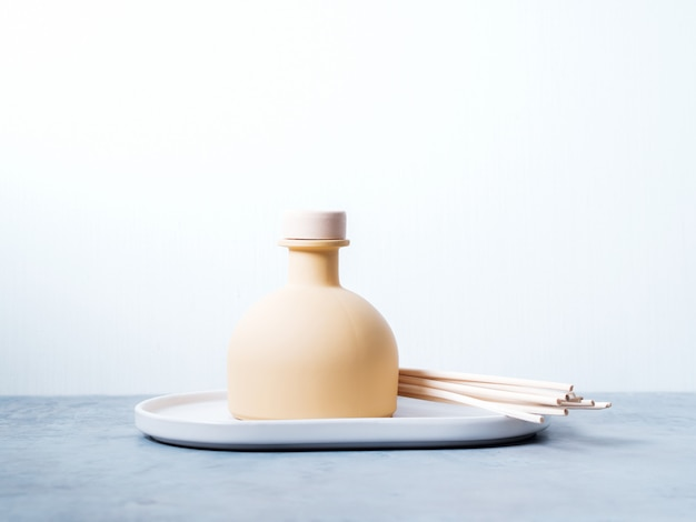 Aroma reed diffuser home fragrance with rattan sticks on a light background Premium Photo