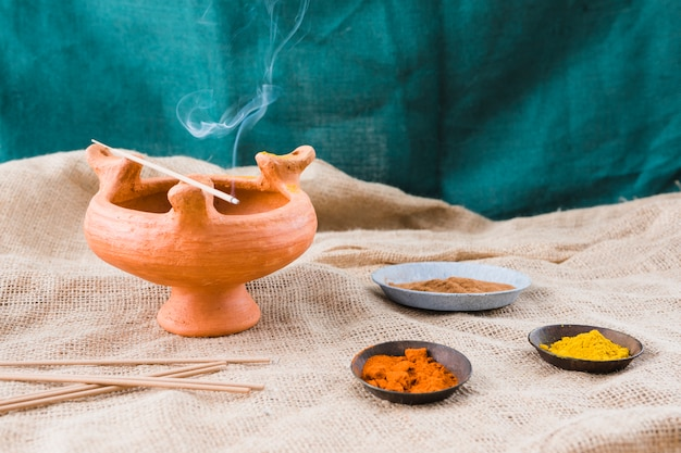 Aroma sticks on bowl near saucers with different spices Free Photo