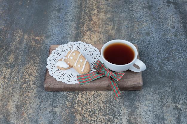 木の板にクリスマスクッキーと白いカップのアロマティー。 無料写真