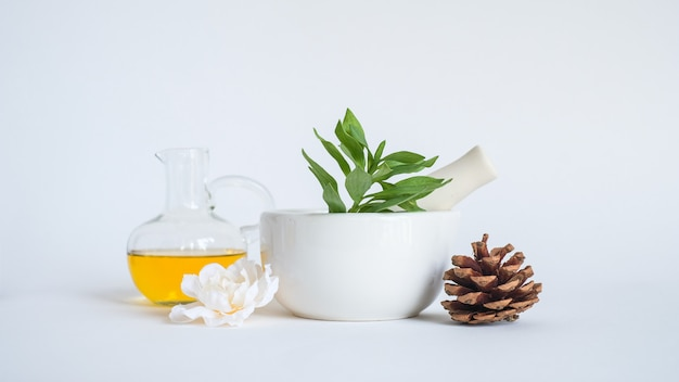 Aromatherapy oil with mortar and natural green leaf. aroma skin beauty spa product concept. Premium Photo