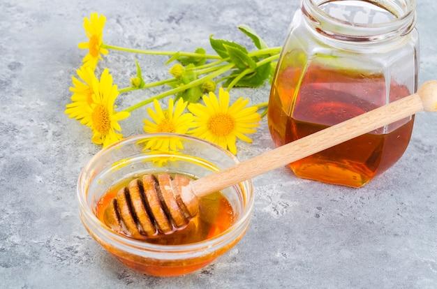 Aromatic flower honey, wild flowers on gray background. Premium Photo