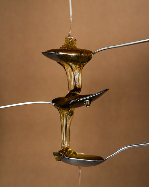 Aromatic honey pouring on spoons Free Photo