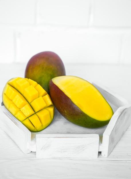 Ароматные спелые манго на белом деревянном фоне, концепция здорового питания и экзотических фруктов Бесплатные Фотографии