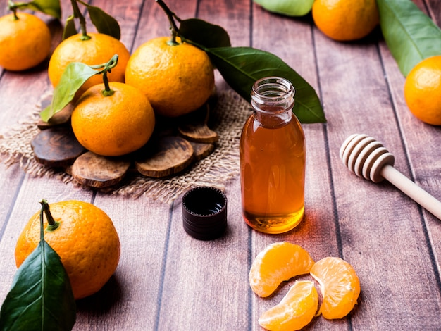 Aromatic tangerine oil, with tangerines on a wooden surface Premium Photo