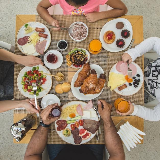 家族arount朝食のテーブルに座って食べる 無料写真