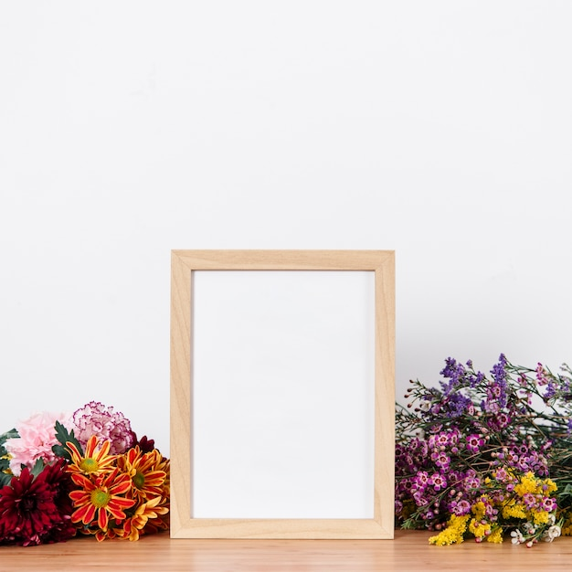 Arranged empty frame and flowers Free Photo