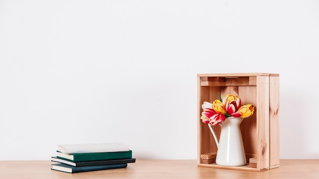 Arranged flowers in box and notebooks Free Photo